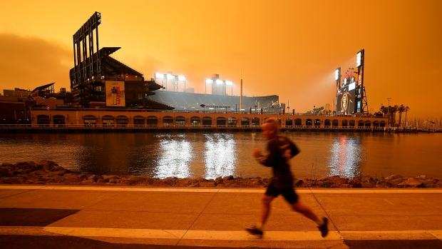 FILE - In this Wednesday, Sept. 9, 2020 file photo, a jogger runs along McCovey Cove outside Oracle Park in San Francisco, under darkened skies from wildfire smoke.Health problems tied to climate change are all getting worse, according to two reports published in the medical journal Lancet on Wednesday, Oct. 20, 2021. An unprecedented Pacific Northwest and Canadian heat wave hit this summer, which a previous study showed couldn't have happened without human-caused climate change. (AP Photo/Tony Avelar)