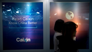 """In this Jan. 18, 2018, file photo, staffers walk past a billboard reading """"Read Caixin - Know China Better"""" at the Caixin Media offices in Beijing. China has removed Caixin Media, one of the country's most liberal business news sites, from a list of official news outlets that can be republished by other internet news providers in the Communist Party's latest move to control the flow of information.(AP Photo/Mark Schiefelbein, File)"""