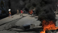 Tires burn in the street as part of an anti-government protest in Port-au-Prince, Haiti, Thursday, Oct. 21, 2021. Haiti is struggling with a spike in gang-related kidnappings after President Jovenel Moïse was fatally shot at his private residence on July 7 and a magnitude 7.2 earthquake killed more than 2,200 people in August. (AP Photo/Matias Delacroix)
