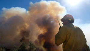 FILE - In this Oct. 13, 2021, file photo, a firefighter watches as smoke rises from a wildfire in Goleta, Calif. Worsening climate change requires that the United States do much more to track and manage flows of migrants fleeing natural disasters. That's the finding of a multiagency study from the Biden administration. President Joe Biden ordered the assessment. (AP Photo/Ringo H.W. Chiu, File)