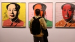 Kourosh Aminzadeh, a student of graphics, looks at China's late leader, Mao Zedong painting series by American artist Andy Warhol at Tehran Museum of Contemporary Art in Tehran, Iran on Oct. 19, 2021. Iranians are flocking to Tehran's contemporary art museum to marvel at American pop artist Andy Warhol's iconic work. (AP Photo/Vahid Salemi)