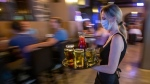 Waitress Kirsten Craig wears a mask to curb the spread of COVID-19 while carrying drinks for guests inside the Blu Martini restaurant in Kingston, Ont., on Friday, July 16, 2021. THE CANADIAN PRESS/Lars Hagberg