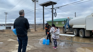 Residents line up to fill containers with potable water in Iqaluit, Nunavut on Thursday, Oct. 14, 2021. THE CANADIAN PRESS/Emma Tranter