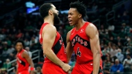 Toronto Raptors' Scottie Barnes (4) reacts with teammate Fred VanVleet after scoring during the second half of an NBA basketball game against the Boston Celtics, Friday, Oct. 22, 2021, in Boston. (AP Photo/Michael Dwyer)