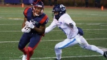 Montreal Alouettes wide receiver Kaion Julien-Grant avoids a tackle by Toronto Argonauts defensive back Chris Edwards during second quarter CFL football action in Montreal on Friday, October 22, 2021. THE CANADIAN PRESS/Paul Chiasson