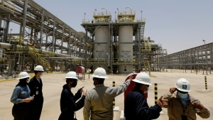 """FILE - In this June 28, 2021, file photo, Saudi Aramco engineers and journalists look at the Hawiyah Natural Gas Liquids Recovery Plant in Hawiyah, in the Eastern Province of Saudi Arabia. One of the world's largest oil producers, Saudi Arabia, announced on Saturday, Oct. 23, it aims to reach """"net zero"""" greenhouse gas emissions by 2060, joining more than 100 countries in a global effort to try and curb man-made climate change. (AP Photo/Amr Nabil, File)"""