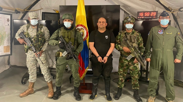 """In this photo released by the Colombian presidential press office, one of the country's most wanted drug traffickers, Dairo Antonio Usuga, alias """"Otoniel,"""" leader of the violent Clan del Golfo cartel, is presented to the media at a military base in Necocli, Colombia, Saturday, Oct. 23, 2021. (Colombian presidential press office via AP)"""