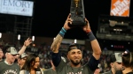 Atlanta Braves' Eddie Rosario holds the Most Valuable Player Trophy after winning Game 6 of baseball's National League Championship Series against the Los Angeles Dodgers Sunday, Oct. 24, 2021, in Atlanta. The Braves defeated the Dodgers 4-2 to win the series. (AP Photo/Brynn Anderson)