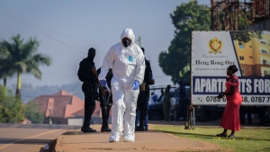 Forensics officers search near the scene of an explosion in the Komamboga suburb of the capital Kampala, Uganda Sunday, Oct. 24, 2021. The explosion at an eatery in Uganda's capital late Saturday was an apparent terrorist act, President Yoweri Museveni said on Sunday. (AP Photo/Nicholas Bamulanzeki)