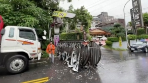 In this image from video, a person walks past a signboard which collapsed in Yilan County, Taiwan after an earthquake on Sunday, Oct. 24, 2021. A 6.5-magnitude quake struck at 1:11 p.m. and was centered near Yilan, a city about 35 kilometers (22 miles) east of Taipei near the northeastern coast, according to the Central Weather Bureau. It was followed seconds later by a 5.4-magnitude quake. (EBC via AP)