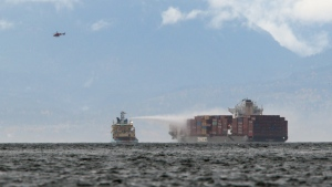 Ships work to control a fire onboard the MV Zim Kingston about eight kilometres from the shore in Victoria, B.C., on Sunday, October 24, 2021. The container ship caught fire on Saturday and 16 crew members were evacuated and brought to Ogden Point Pier. THE CANADIAN PRESS/Chad Hipolito