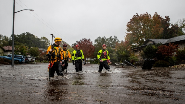 Santa Rosa firefighters check for residents trapped by floodwaters on Brookhaven Drive in Santa Rosa, Calif., on Sunday, Oct. 24, 2021. (AP Photo/Ethan Swope)