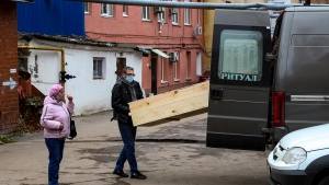"""Ramilya Shigalturina stands in the courtyard of a morgue at Infectious Hospital No. 5 in Nizhny Novgorod, Russia, Wednesday, on Oct. 20, 2021, as a worker moves a coffin containing the body of her grandmother, who died of COVID-19. Shigalturina said the disease was """"really dreadful and dangerous,"""" and she begged Russians to get vaccinated. The resident of Nizhny Novgorod, the country's fifth-largest city, said her 83-year-old grandmother, who was unvaccinated, """"died right away after catching it."""" (AP Photo/Roman Yarovitcyn)"""