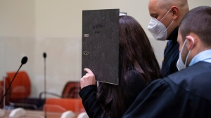 Defendant Jennifer W. arrives in a courtroom for her trial in Munich, Germany, Monday, Oct. 25, 2021. The woman from Lohne in Lower Saxony is charged with murder and war crimes. As an IS supporter in Iraq, she is said to have stood idly by while a small Yazidi girl was chained in a courtyard and died of thirst. (Sven Hoppe/dpa via AP)
