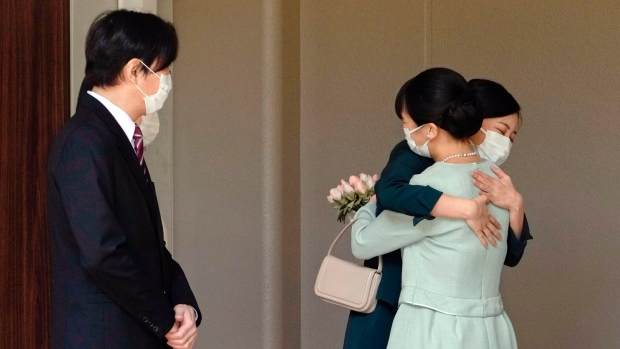 Japan's Princess Mako, right, hugs her sister Princess Kako, watched by her parents Crown Prince Akishino and Crown Princess Kiko, before leaving her home in Akasaka Estate in Tokyo Tuesday, Oct. 26, 2021. Mako and her commoner boyfriend Kei Komuro tied the knot Tuesday without wedding celebration in a marriage that has split the public opinion over her would-be mother-in-law's financial controversy. (Koki Sengoku/Kyodo News via AP)
