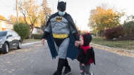 Marino Rossi and granddaughter Ruby Bishyk go Trick or Treating on Halloween in Montreal, Saturday, October 31, 2020, as the COVID-19 pandemic continues in Canada and around the world. THE CANADIAN PRESS/Graham Hughes