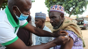 A Muslim man is administered a Moderna COVD-19 vaccination outside the Kuje, Central Mosque outskirts of Abuja, Friday, Oct. 8, 2021. Nigeria has begun the second rollout of COVID-19 vaccines as it aims to protect its population of more than 200 million amid an infection surge in a third wave of the pandemic. (AP Photo/Gbemiga Olamikan)