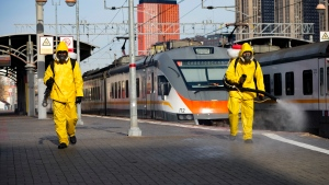Employees of the Federal State Center for Special Risk Rescue Operations of Russia Emergency Situations disinfect Savyolovsky railway station in Moscow, Russia, Tuesday, Oct. 26, 2021. The daily number of COVID-19 deaths in Russia hit another high Tuesday amid a surge in infections that forced the Kremlin to order most Russians to stay off work starting this week. (AP Photo/Alexander Zemlianichenko)