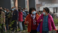 Women wearing face masks to help curb the spread of the coronavirus chat each other as they walk by masked residents line up to receive booster shots against COVID-19 at a vaccination site in Beijing, Monday, Oct. 25, 2021. A northwestern Chinese province heavily dependent on tourism closed all tourist sites Monday after finding new COVID-19 cases. (AP Photo/Andy Wong)