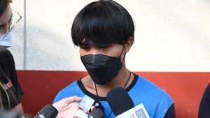 A Myanmar national identified as Song, one of two painters rescued from a high-rise condominium in Thailand, talks to reporters at Pak Kret police station in Nonthaburi near Bangkok, Wednesday, Oct. 27, 2021. A resident of the building cut the support rope for the two painters, apparently angry she wasn't told they would be doing work, and left them hanging above the 26th floor until a couple rescued them, police said Wednesday. The woman is facing charges of attempted murder, according to a police official. (AP Photo/Surat Sappakun)