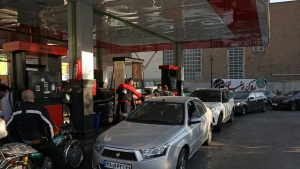 """People fill their cars at a gas station in Tehran, Iran Wednesday, Oct. 27, 2021. Iran's President Ebrahim Raisi said Wednesday that a cyberattack which paralyzed every gas station in the Islamic Republic was designed to get """"people angry by creating disorder and disruption."""" Long lines snaked around the pumps a day after the incident began as some stations began selling fuel again although at higher, unsubsidized prices. (AP Photo/Vahid Salemi)"""