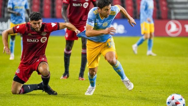 Toronto FC midfielder Jonathan Osorio (21) pulls on the jersey of Philadelphia Union midfielder Alejandro Bedoya (11) during first half MLS action in Toronto on Wednesday, October 27, 2021. THE CANADIAN PRESS/Evan Buhler