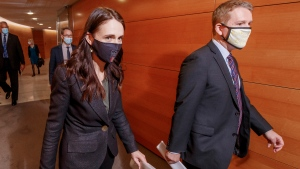 FILE - New Zealand Prime Minister Jacinda Ardern, left, walks with COVID-19 Response Minister Chris Hipkins to a press conference at Parliament in Wellington, New Zealand Monday, Oct. 11, 2021.