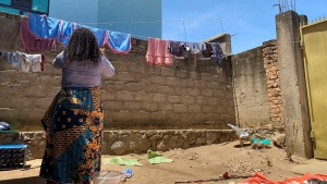 """Reby hangs laundry outside her home in Beni, eastern Congo, on Saturday, May 1, 2021. In 2019, she met World Health Organization Dr. Boubacar Diallo, of Canada, when he came intoa mobile phoneshop where she was working. He asked her to talk about """"important things"""" with him in a hotel and gave her $100 for """"transport costs,"""" she told the AP. """"My God, a beautiful girl like you who gets $60 a month is not enough,"""" he said, according to Reby. """"You are a big girl and if you sleep with me, you are going to be a high-ranking member of the Ebola response in Beni and you are going to receive around $800 a month."""" She said she refused Diallo's offer, but continued to see him when he came into her shop. """"From that day on, he always called me the difficult girl,"""" she said. (AP Photo/Kudra Maliro)"""