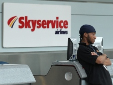 A worker at Pearson International Airport in Toronto stands in front of Skyservice Airlines' check-in counter Wednesday, March 31, 2010. (THE CANADIAN PRESS/Darren Calabrese)