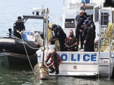 Police remove a barrel believed to be containing a body encased in concrete from the Toronto harbour on Sunday, May 23, 2010.