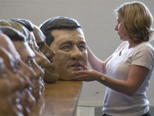 Karen Palmer of Oxfam Canada inspects a Stephen Harper papier mache head at their Toronto office, on Monday, June 14, 2010. (Adrien Veczan / THE CANADIAN PRESS)