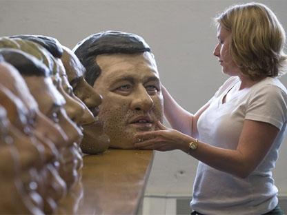 Karen Palmer of Oxfam Canada inspects a Stephen Harper papier mache head at their Toronto office, on Monday, June 14, 2010. (Adrien Veczan / THE CANADIAN PRESS)