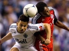 Vancouver Whitecaps player Davide Chiumiento, left, and Toronto FC's Julian de Guzman jump for the ball during the second half of a Canadian Championship soccer game in Vancouver, B.C., on Wednesday, May 16, 2012. (THE CANADIAN PRESS/Darryl Dyck)