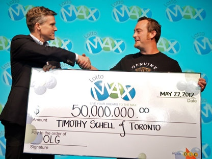 Rod Phillips (left), OLG�s President and CEO, presents Timothy Schell with his $50-million winning Lotto Max lottery cheque in Toronto on Tuesday, May 22, 2012. (THE CANADIAN PRESS/HO-Ontario Lottery and Gaming Corporation)