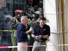 "Kenya paramilitary soldiers secure the area as American investigators work at the site of an explosion to assist Kenyan officials in Nairobi, Kenya on Tuesday, May 29, 2012. An explosion ripped through a building full of small shops in Nairobi a day earlier, injuring at least 33 people, including a woman who blamed the blast on a ""bearded man"" who left behind a bag shortly before the detonation. (AP Photo/Khalil Senosi)"
