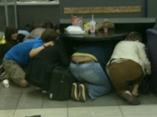 People take cover underneath a table at the food court of the Eaton Centre after shots were fired inside the mall on June 2, 2012. (Twitter)
