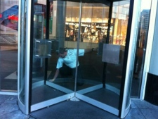 A security guard unlocks a door at Eaton Centre on Monday, June 4, 2012. The mall reopened following a deadly shooting two days earlier. (CTV/Tamara Cherry)