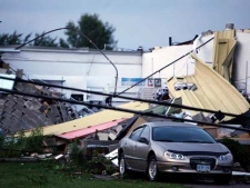 A car sits in front of a damaged building in Midland Ontario, Wednesday June 23, 2010 after a severe storm harbouring a suspected tornado tore through the town. (Benjamin Ricetto/THE CANADIAN PRESS)