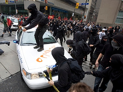 Activists attack a police car in Toronto's financial district during the G20 Summit Saturday, June 26, 2010. (THE CANADIAN PRESS/Darren Calabrese)