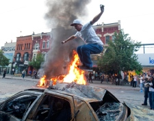A protester jumps on a burnt out car as a police car burns in the background during an anti-G20 demonstration Saturday, June 26, 2010 in Toronto. (THE CANADIAN PRESS/Ryan Remiorz)