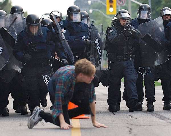 A protester crawls as he is chased by police officers during G20 demos in Toronto on Saturday, June 26, 2010. (THE CANADIAN PRESS/Adrien Veczan)