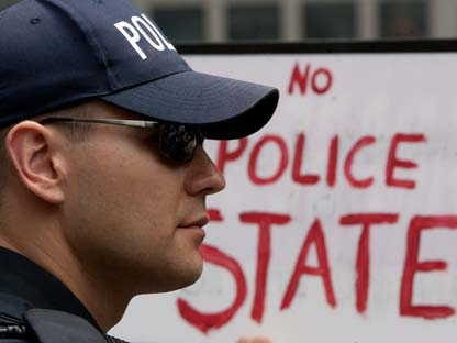 A police officer looks on in front of a placard during a demonstration as the G20 summit draws to a close in Toronto, Sunday, June 27, 2010. (Chris Young/THE CANADIAN PRESS)
