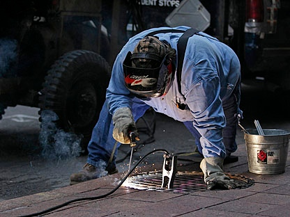 Mike Boyle welds a manhole shut along Bay Street in downtown Toronto, Sunday, June 27, 2010, as an additional security measure in the wake of riots in downtown Toronto the night before during the G20 Summit. (AP Photo/Carolyn Kaster)