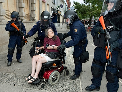 RCMP riot squad officers escort a woman in a wheelchair away from a demonstration at the conclusion of the G20 summit in Toronto on Sunday, June 27, 2010. (THE CANADIAN PRESS/Frank Gunn)