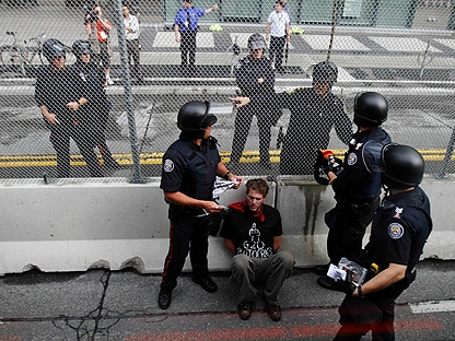 A demonstrator is arrested by Canadian police officers near the fence that surrounds the G20 Summit venue in Toronto, Canada, Saturday June 26, 2010. (AP Photo/Lefteris Pitarakis)