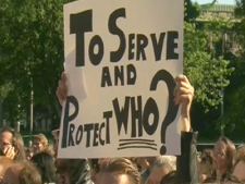 A protester holds up a sign saying 'To Serve and Protect Who?' at a rally on Thursday, July 1, 2010 to demand an inquiry into police conduct during the G20 Summit in Toronto.