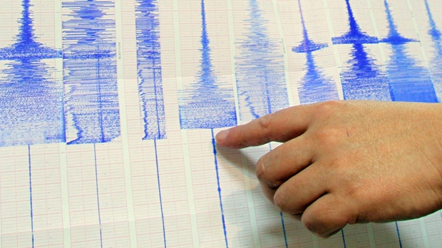 A man points to Richter scale graphs.