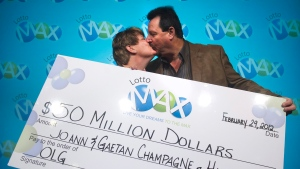 Lotto Max winners JoAnn Champagne, left, and her husband Gaetan Champagne share a kiss after receiving their $50-million cheque at the Ontario Lottery and Gaming Corp. in Toronto on Wednesday, Feb. 29, 2012. The two won the jackpot on Dec. 30, 2011. (Nathan Denette / THE CANADIAN PRESS)