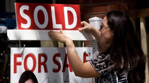 "A real estate agent puts up a ""sold"" sign in front of a house in Toronto on Tuesday, April 20, 2010. (Darren Calabrese / THE CANADIAN PRESS)"