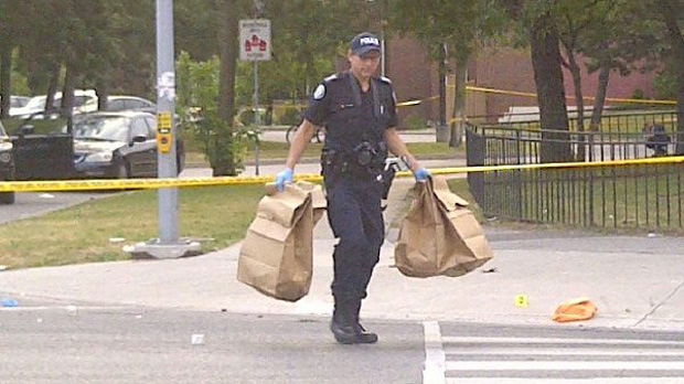 A Toronto police forensic investigator carries evidence at the scene of a deadly shooting on Danzig Street in Scarborough on Tuesday, July 17, 2012. (CP24/Katie Simpson)